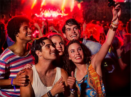 Friends taking self-portrait with camera phone at music festival Stock Photo - Premium Royalty-Free, Code: 6113-07564776