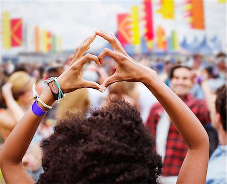 Woman forming heart-shape with hands at music festival Stock Photo - Premium Royalty-Free, Code: 6113-07564842