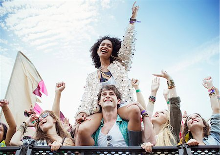 Cheering woman on man's shoulders at music festival Stock Photo - Premium Royalty-Free, Code: 6113-07564849