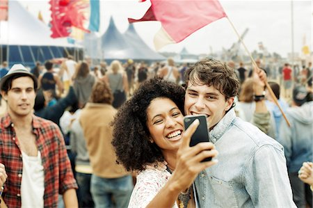 Couple taking self-portrait with camera phone at music festival Stock Photo - Premium Royalty-Free, Code: 6113-07564857