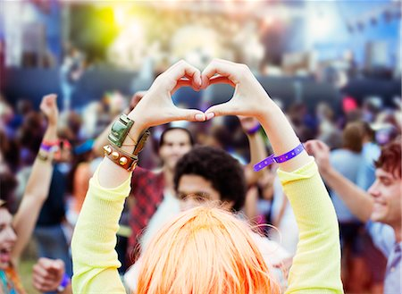 Woman forming heart-shape with hands at music festival Stock Photo - Premium Royalty-Free, Code: 6113-07564860