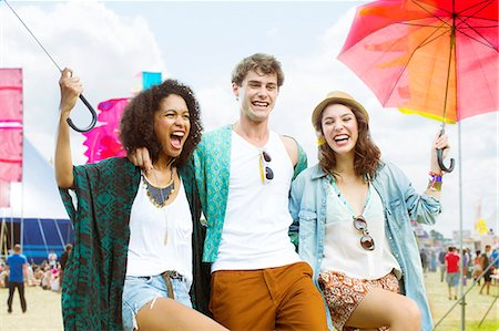 Portrait of friends with umbrellas at music festival Stock Photo - Premium Royalty-Free, Code: 6113-07564875