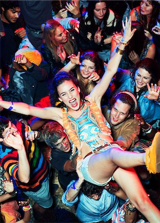 entertainment - Enthusiastic woman crowd surfing at music festival Stock Photo - Premium Royalty-Free, Code: 6113-07564889