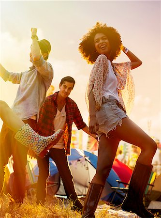 Friends dancing outside tents at music festival Stock Photo - Premium Royalty-Free, Code: 6113-07564891