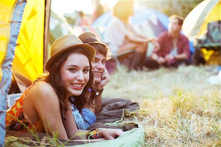Portrait of couple laying in tent at music festival Stock Photo - Premium Royalty-Free, Code: 6113-07564897