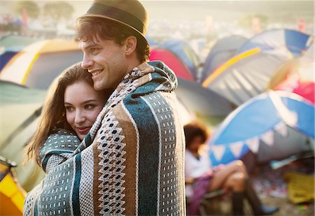 Couple wrapped in a blanket outside tents at music festival Stock Photo - Premium Royalty-Free, Code: 6113-07564899