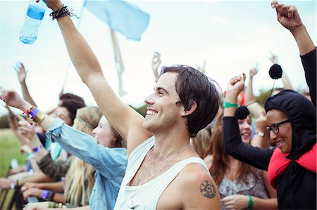 Man with water bottle cheering at music festival Stock Photo - Premium Royalty-Free, Code: 6113-07564827