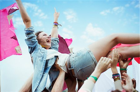 Enthusiastic woman crowd surfing at music festival Stock Photo - Premium Royalty-Free, Code: 6113-07564838