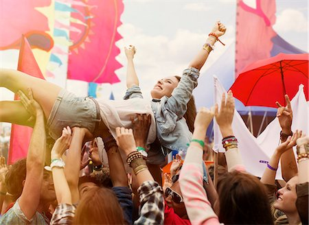 Woman crowd surfing at music festival Stock Photo - Premium Royalty-Free, Code: 6113-07564839
