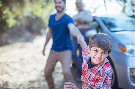 Happy boy dragging father by the arm outside car Stock Photo - Premium Royalty-Free, Code: 6113-07564947