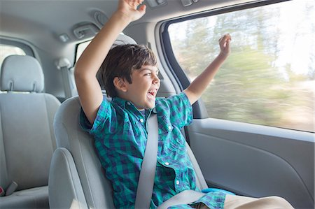 road trip - Enthusiastic boy cheering in back seat of car Stock Photo - Premium Royalty-Free, Code: 6113-07564944