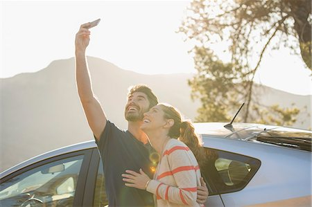 Happy couple taking self-portrait with camera phone outside car Stock Photo - Premium Royalty-Free, Code: 6113-07564946