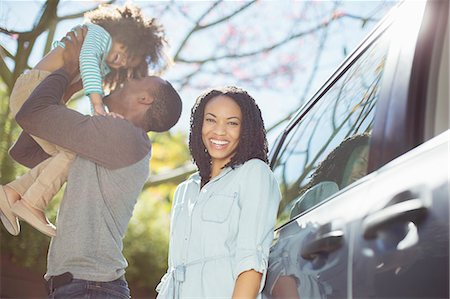 Portrait of happy woman with husband and daughter outside car Stock Photo - Premium Royalty-Free, Code: 6113-07564957