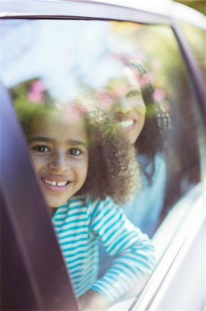Portrait of smiling car looking out car window Stock Photo - Premium Royalty-Free, Code: 6113-07564963