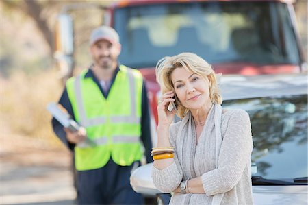 Roadside mechanic behind woman on cell phone Stock Photo - Premium Royalty-Free, Code: 6113-07564965