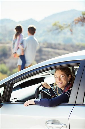 Portrait of smiling woman inside of car Stock Photo - Premium Royalty-Free, Code: 6113-07564966
