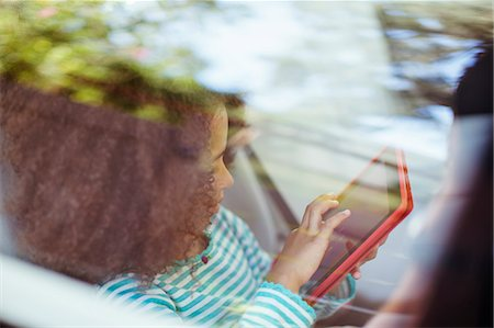Girl using digital tablet in back seat of car Stock Photo - Premium Royalty-Free, Code: 6113-07564989
