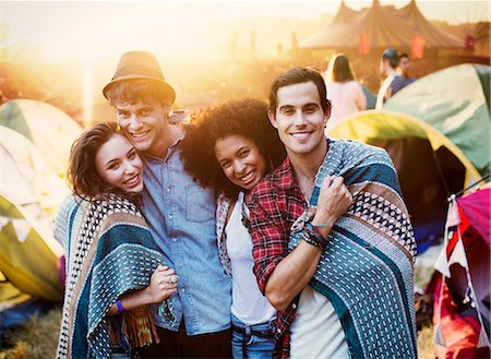 Portrait of couples wrapped in a blanket outside tents at music festival Stock Photo - Premium Royalty-Free, Code: 6113-07564900