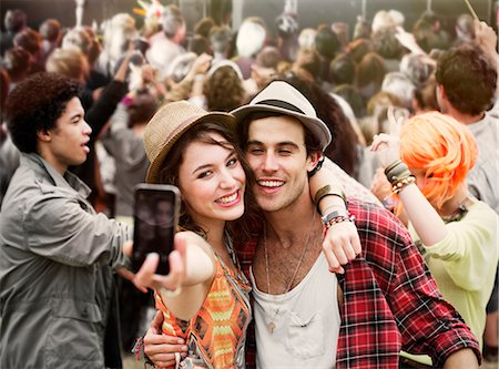Couple taking self-portrait at music festival Stock Photo - Premium Royalty-Free, Code: 6113-07564926