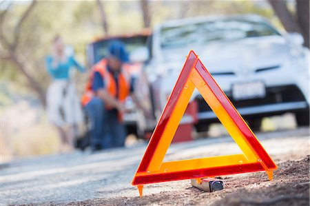 safety - Warning triangle on road with mechanic in background Stock Photo - Premium Royalty-Free, Code: 6113-07564933