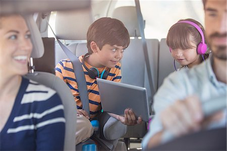 Brother and sister sharing digital tablet in back seat of car Stock Photo - Premium Royalty-Free, Code: 6113-07564930