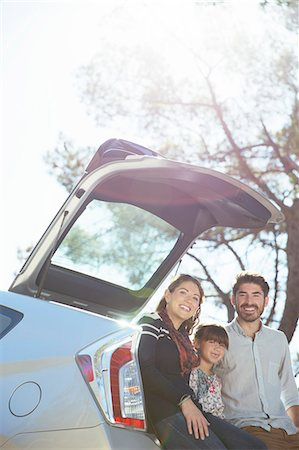 Portrait of smiling family sitting against rear of car Stock Photo - Premium Royalty-Free, Code: 6113-07564931