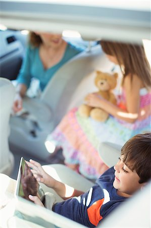 elementary age - Boy using digital tablet in back seat of car Stock Photo - Premium Royalty-Free, Code: 6113-07565041