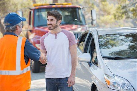 Man shaking hands with roadside mechanic Stock Photo - Premium Royalty-Free, Code: 6113-07565053