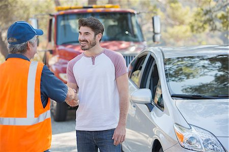 Man shaking hands with roadside mechanic Stock Photo - Premium Royalty-Free, Code: 6113-07565053