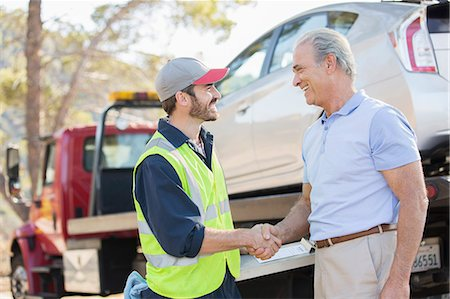 Roadside mechanic and man shaking hands Stock Photo - Premium Royalty-Free, Code: 6113-07565078