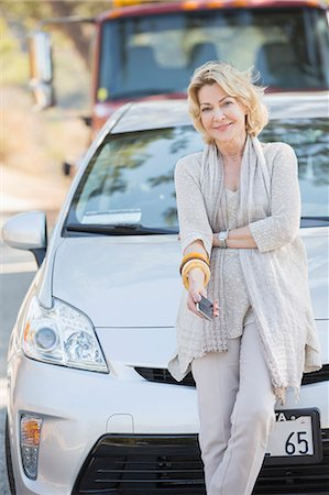 Portrait of smiling woman waiting for roadside assistance Stock Photo - Premium Royalty-Free, Code: 6113-07565020