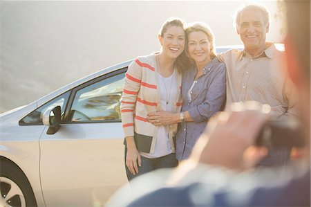 Man photographing family outside car Stock Photo - Premium Royalty-Free, Code: 6113-07565025