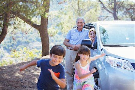 Grandparents watching grandchildren running outside car Stock Photo - Premium Royalty-Free, Code: 6113-07565031