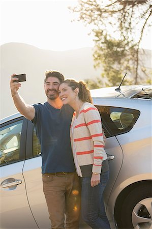 Couple taking self-portrait with camera phone outside car Stock Photo - Premium Royalty-Free, Code: 6113-07565038