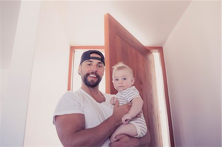 Portrait of smiling father holding baby son in doorway Stock Photo - Premium Royalty-Free, Code: 6113-07565155