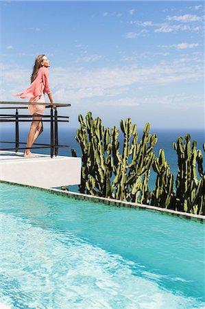 Woman basking in sun on poolside balcony overlooking ocean Stock Photo - Premium Royalty-Free, Code: 6113-07565192