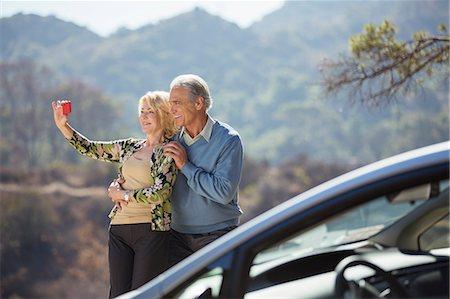 Senior couple taking self-portrait at roadside outside car Stock Photo - Premium Royalty-Free, Code: 6113-07565113