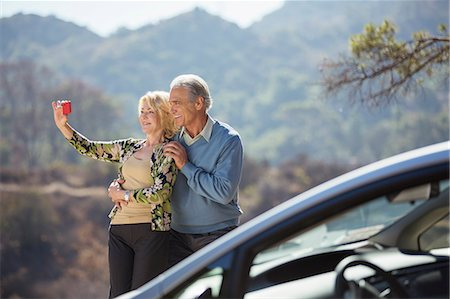 Senior couple taking self-portrait at roadside outside car Stock Photo - Premium Royalty-Free, Code: 6113-07565113