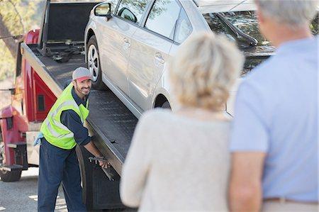 Senior couple watching roadside mechanic prepare to tow car Stock Photo - Premium Royalty-Free, Code: 6113-07565117
