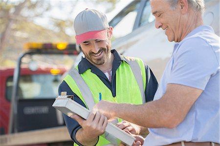 Man signing paperwork for roadside mechanic Stock Photo - Premium Royalty-Free, Code: 6113-07565114