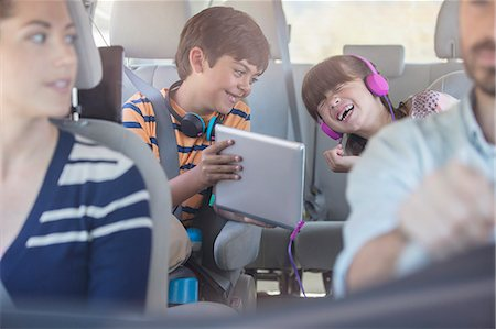 Happy brother and sister using digital tablet in back seat of car Stock Photo - Premium Royalty-Free, Code: 6113-07565122