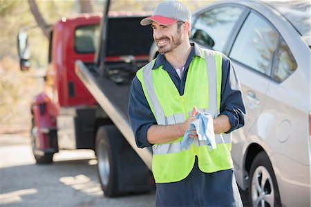 Roadside mechanic wiping hands with cloth next to tow truck Stock Photo - Premium Royalty-Free, Code: 6113-07565134