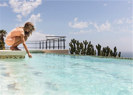 Woman dipping hand in swimming pool Stock Photo - Premium Royalty-Free, Code: 6113-07565200