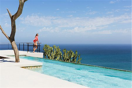 rich lifestyle - Woman standing on poolside balcony overlooking ocean Stock Photo - Premium Royalty-Free, Code: 6113-07565217
