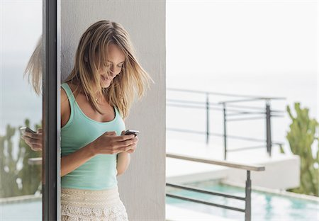 Smiling woman texting with cell phone on patio Stock Photo - Premium Royalty-Free, Code: 6113-07565222