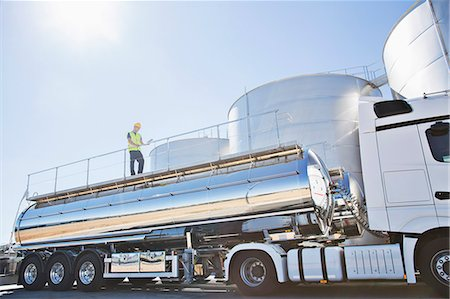 side view tractor trailer truck - Worker on platform above stainless still milk tanker Stock Photo - Premium Royalty-Free, Code: 6113-07565342