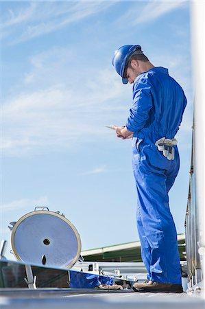 Worker using digital tablet on platform Stock Photo - Premium Royalty-Free, Code: 6113-07565345