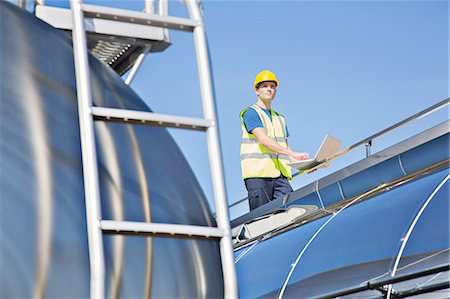 side view tractor trailer truck - Worker using laptop on platform above stainless steel milk tanker Stock Photo - Premium Royalty-Free, Code: 6113-07565362
