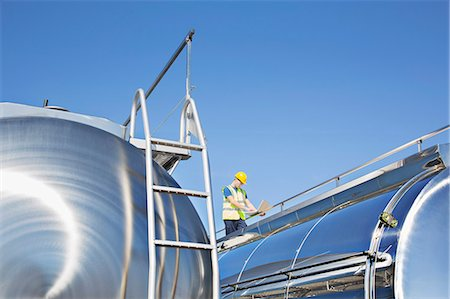 side view tractor trailer truck - Worker using laptop on platform above stainless steel milk tanker Stock Photo - Premium Royalty-Free, Code: 6113-07565364