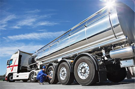 side view tractor trailer truck - Worker checking tire on stainless steel milk tanker Stock Photo - Premium Royalty-Free, Code: 6113-07565387